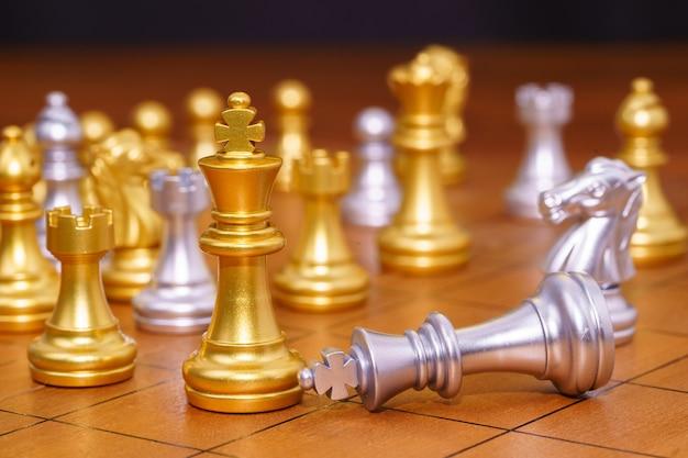 Gold king schachfigur und verschiedene schachfiguren stehen auf holzschachbrett, konzept des führungsspiels der strategie Premium Fotos