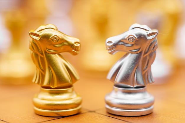 Gold und siver pferd des schachspiels im spiel auf schachbrett Premium Fotos