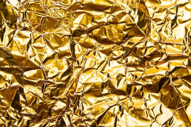 Gold zerknitterte folienpapierbeschaffenheit Premium Fotos