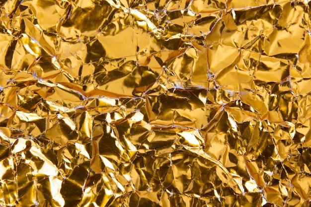Gold zerknitterter folienpapier-beschaffenheitshintergrund. Premium Fotos