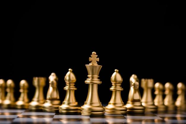 Golden king schach stehen vor anderen schachfiguren. konzept zur planung von führungsgeschäfts-teamwork und marketingstrategien. Premium Fotos