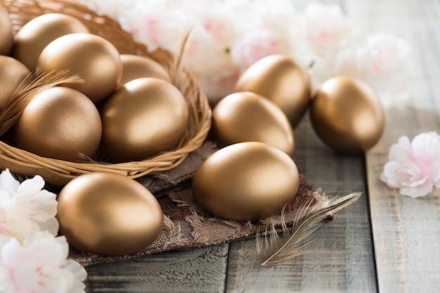 Golden von ostereiern im nest mit rosa blume und feder Premium Fotos
