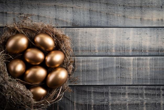 Golden von ostereiern im nest und von der feder auf hölzernem hintergrund. Premium Fotos