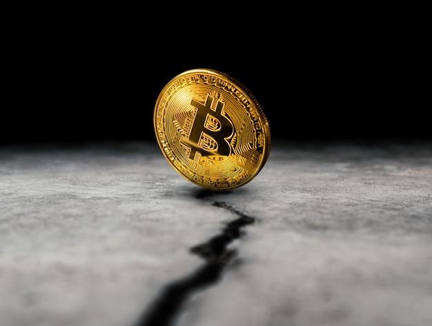 Goldene bitcoin münze auf gebrochenem konkretem bodenkrypto währungshintergrundkonzept. Premium Fotos