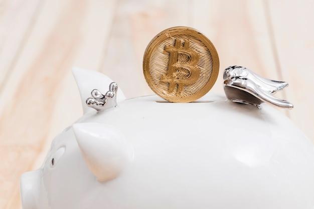 Goldene bitcoins über dem schlitz des weißen sparschweins Kostenlose Fotos