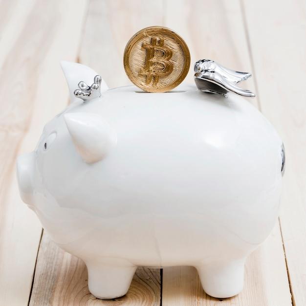 Goldene bitcoins über dem schlitz von weißem piggybank auf holztisch Kostenlose Fotos