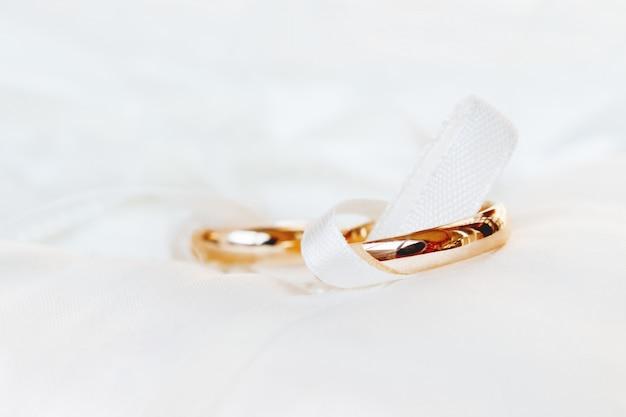Goldene eheringe auf weißem silk hintergrund. hochzeitsdetails. Premium Fotos