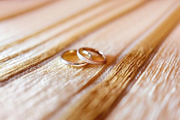 Goldene eheringe mit diamanten auf beige gewebehintergrund. Premium Fotos