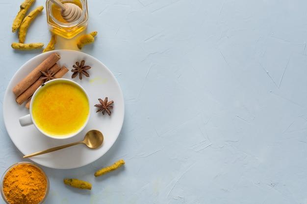Goldene gelbwurzmilch mit honig und bestandteilen auf blau. Premium Fotos