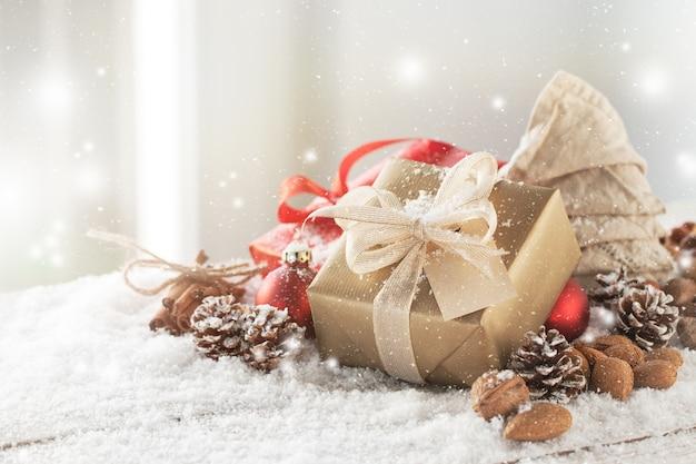 Goldene geschenk mit weißen bogen auf weihnachtskugeln Kostenlose Fotos