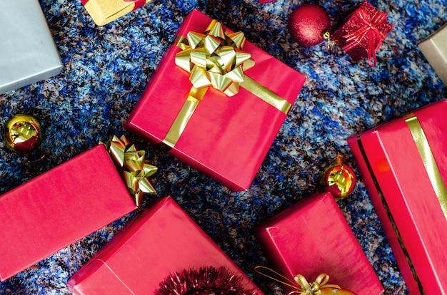 Goldene geschenkbox und rotes band auf farbhintergrund Premium Fotos