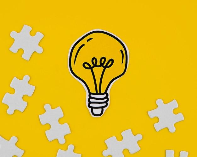Goldene glühlampe der nahaufnahme mit puzzlespielstücken Kostenlose Fotos