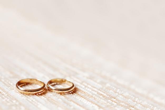 Goldene hochzeit ringe auf beige. hochzeitsdetails, symbol der liebe und heirat. Premium Fotos