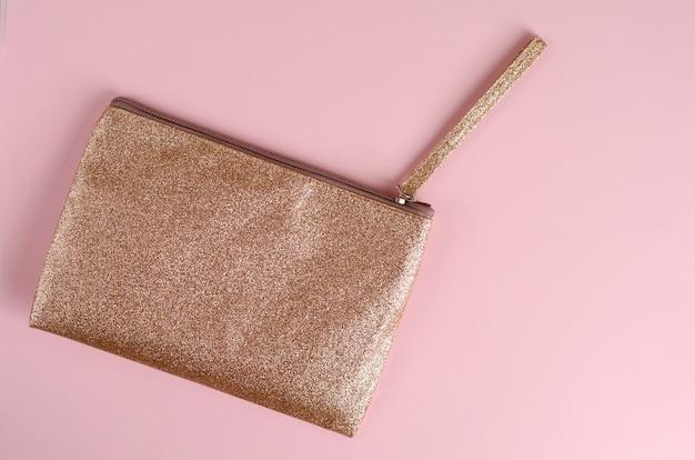 Goldene kosmetiktasche auf pastellrosa Premium Fotos