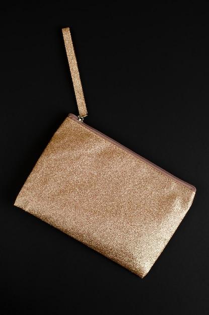 Goldene kosmetiktasche auf schwarzem. Premium Fotos