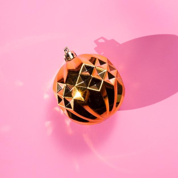 Goldene kugel der draufsicht auf rosa hintergrund Kostenlose Fotos