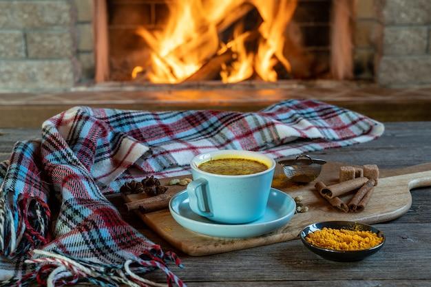 Goldene latte-milch mit kurkuma und gewürzen vor dem gemütlichen kamin. gesundes coronavirus-schutzgetränk. Premium Fotos