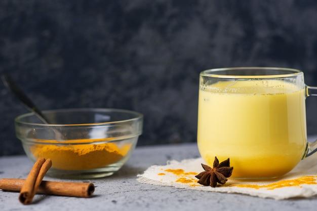 Goldene milch der indischen gewürzgelbwurz in einem becher auf einer dunklen steintabelle Premium Fotos