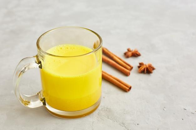 Goldene milch mit kurkuma in einer transparenten tasse, anissternen und zimtstangen. gesundes essenkonzept. Premium Fotos
