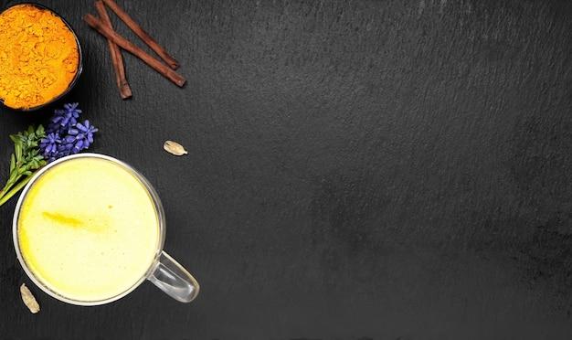 Goldene milch mit kurkuma und anderen gewürzen auf einer schwarzen oberfläche Kostenlose Fotos