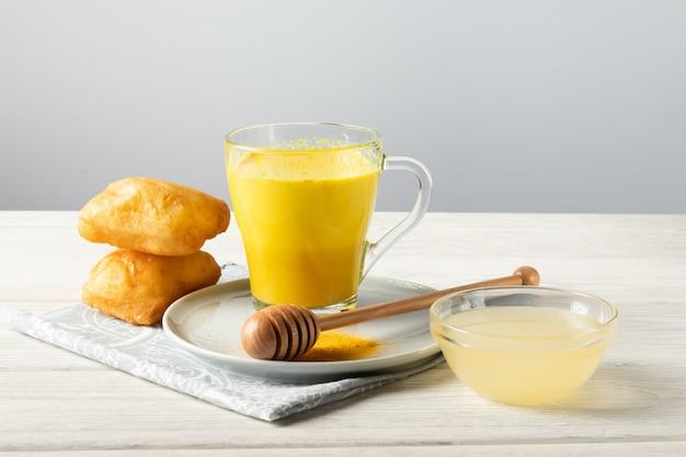 Goldene milch mit kurkuma und honig, ein traditionelles indisches getränk Premium Fotos