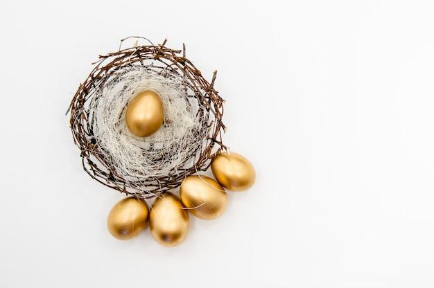 Goldene ostereier in einem kasten mit goldenen sternen auf weißem hintergrund Premium Fotos