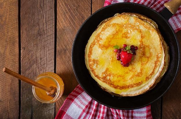 Goldene pfannkuchen mit preiselbeermarmelade und honig im rustikalen stil. ansicht von oben Kostenlose Fotos