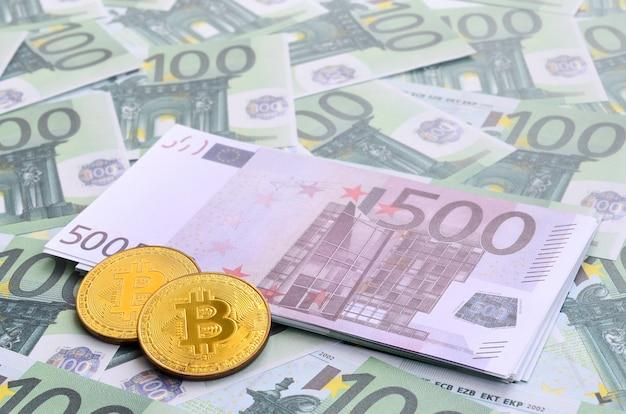 Goldene physische bitcoins liegt auf einer reihe grüner währungsbezeichnungen von 100 euro Premium Fotos