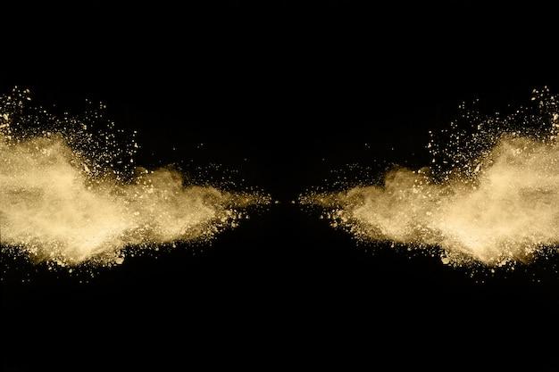Goldene pulverexplosion auf schwarzem hintergrund. Premium Fotos