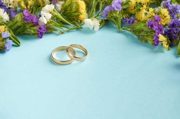 Goldene ringe mit farbigen blumen auf blauer oberfläche, heiratsschablone. Premium Fotos