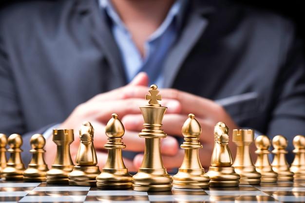 Goldene schachfiguren auf schachbrett und vor geschäftsmann. Premium Fotos