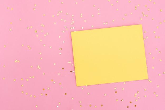Goldene und rosa konfettis, die aus weißem umschlag auf pastellrosahintergrund heraus gießen. Premium Fotos