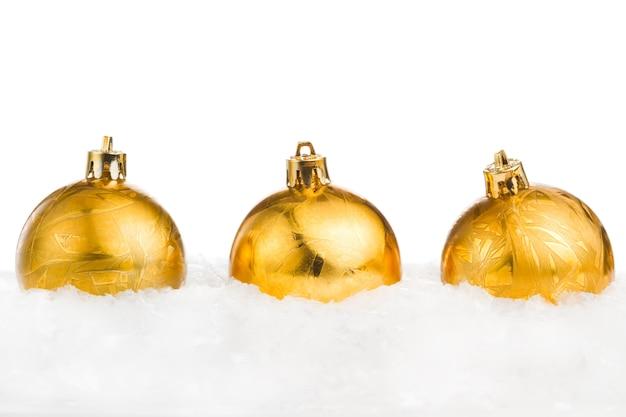 Goldene weihnachtsbälle auf dem eis und schnee lokalisiert auf weißem backgro Premium Fotos