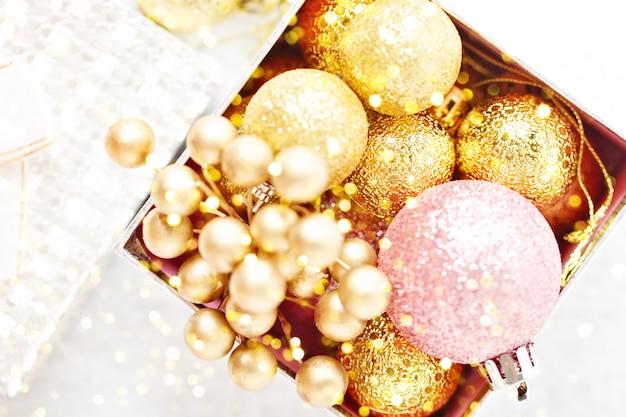 Goldene weihnachtsbälle auf einem hellen hintergrund. ansicht von oben. weihnachten hintergrund. Premium Fotos