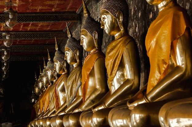 Goldener buddha neben alten wänden in den thailändischen tempeln Premium Fotos