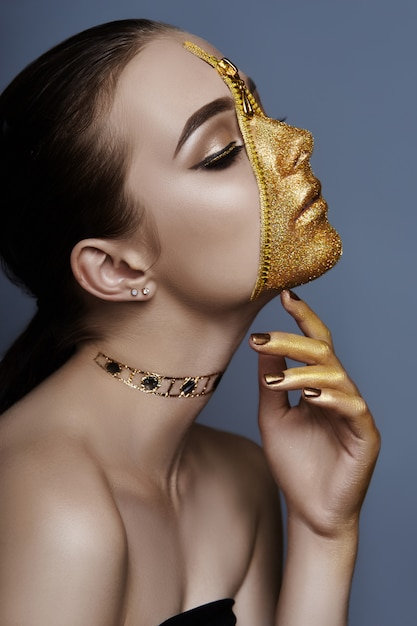 Goldener farbreißverschluss des kreativen grimmigen make-upgesichtsmädchens Premium Fotos