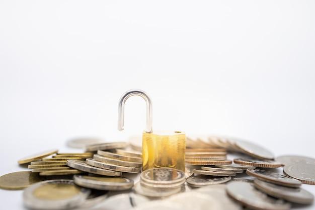 Goldener hauptschlüssel entriegelt auf stapel und stapel von münzen auf weiß Premium Fotos