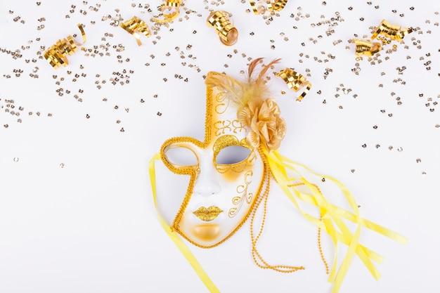Goldener konfetti-rahmen und goldene maske Kostenlose Fotos