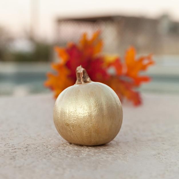 Goldener kürbis mit orangenblättern für dekoration Premium Fotos
