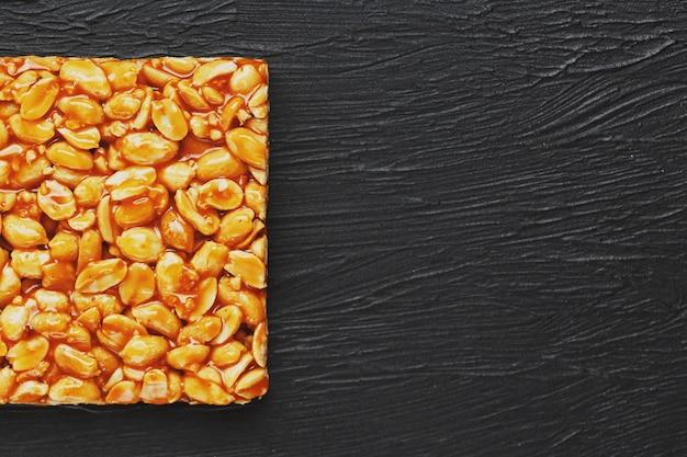Goldener steinpilz kozinaki von den gebratenen erdnussbohnen-energieriegeln. schwarzer struktureller hintergrund, draufsicht Premium Fotos