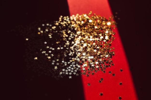 Goldener stern confetti im harten licht mit schatten Premium Fotos