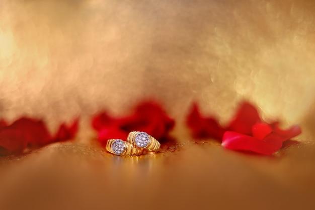 Goldener verlobungsring mit rotrosenblume Premium Fotos