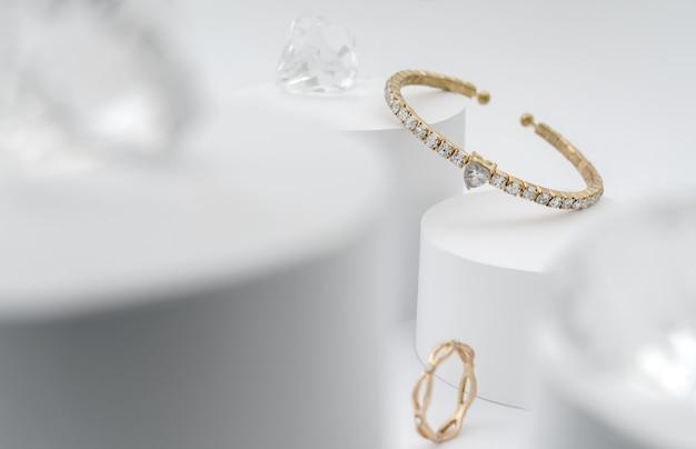 Goldenes armband mit diamanten zwischen diamanten auf weißer plattform Premium Fotos