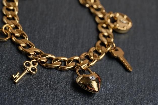 Goldenes armband mit schlüsseln und herz Premium Fotos