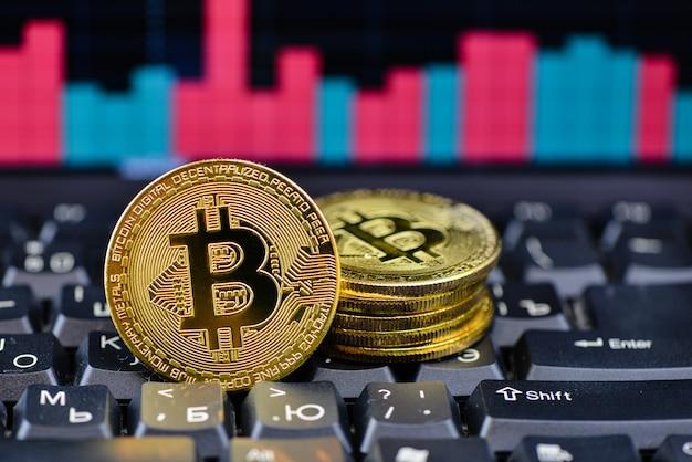 Goldenes bitcoin auf notizbuchtastatur mit diagramm auf hintergrund Premium Fotos