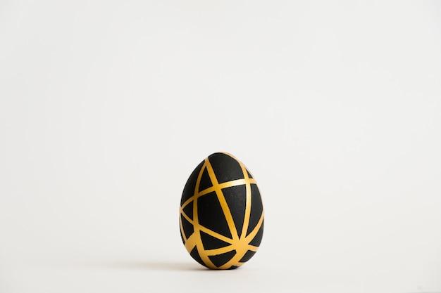 Goldenes ei ostern mit dem geometrischen schwarzen muster lokalisiert auf weißem hintergrund Premium Fotos