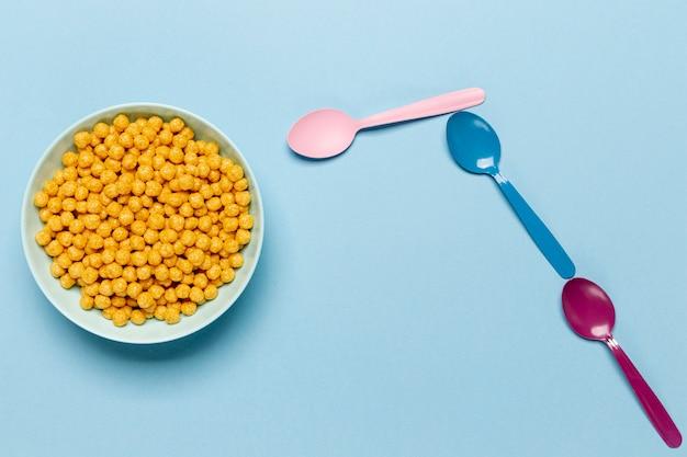 Goldenes getreide in der blauen schüssel mit löffelebenenlage Kostenlose Fotos