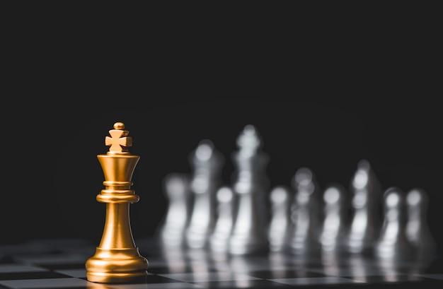 Goldenes königschach steht allein unter dem silbernen schachfeind auf der gegenüberliegenden seite Premium Fotos