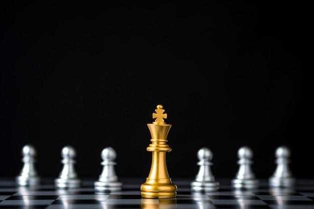 Goldenes königschach vor silbernem bauernschach auf schachbrett und schwarzem hintergrund. Premium Fotos