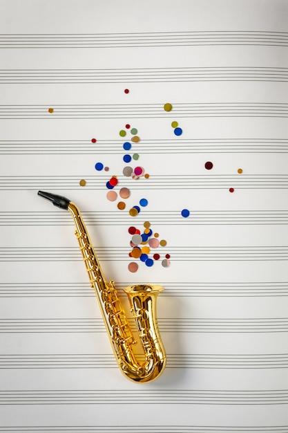 Goldenes saxophon mit farbigen pailletten auf musiknotizbuchhintergrund. jazz day konzept. Premium Fotos